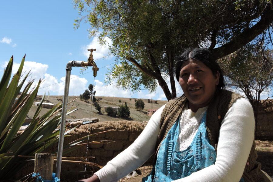 mujer-sonriedo-por-agua-potable-en-su-casa-AYNI